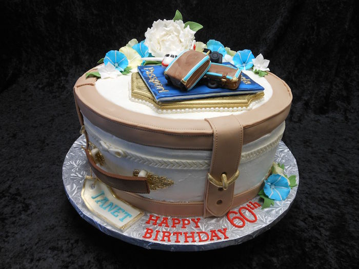 round cake made to look like a suitcase, in white and beige, with golden buckle details, topped with fresh flowers, a passport and small suitcases, made of fondant, happy 60th birthday, written in red frosting