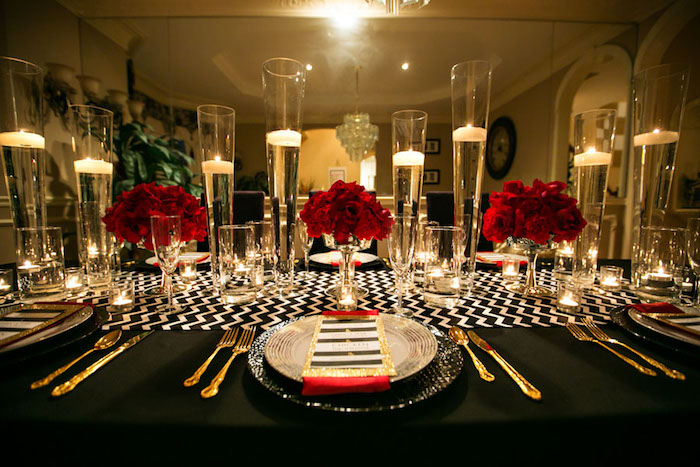 table cloth in black, with white zig-zag details, on a table set for a fancy dinner, gold cutlery and candles in tall glasses