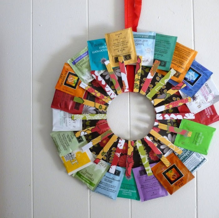 wreath made of tea packets, in different colors, secured with patterned clothes pegs, handmade gift ideas, mounted on a white wall