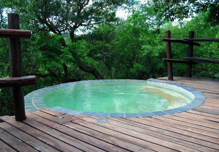 circular pool on a terrace, covered in wooden planks, and featuring a wooden fence, pool patio ideas, with a forest view
