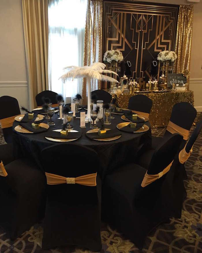 60th birthday color, round black table, with black chairs, decorated with a white ostrich feather center piece, and gold details, art deco motifs, jazz age birthday party