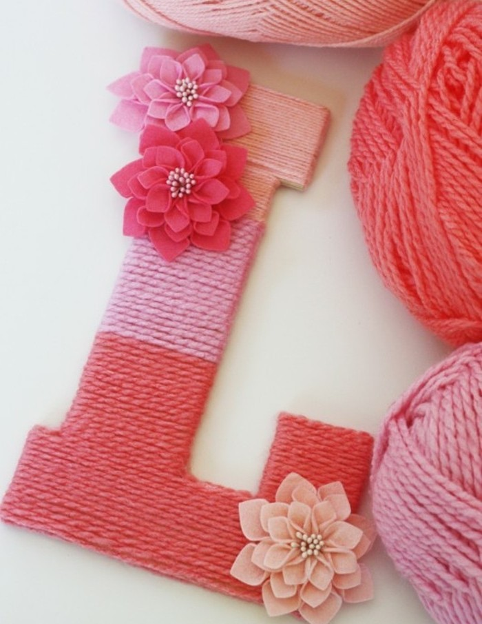 yarn in three different shades of pink, wrapped around a big L shape, decorated with pink flower ornaments, cute gift ideas, three balls of yarn nearby