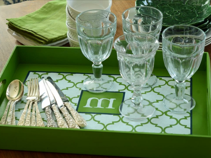 cutlery and four glasses, on a green monogrammed serving tray, decorated with a symmetrical pattern