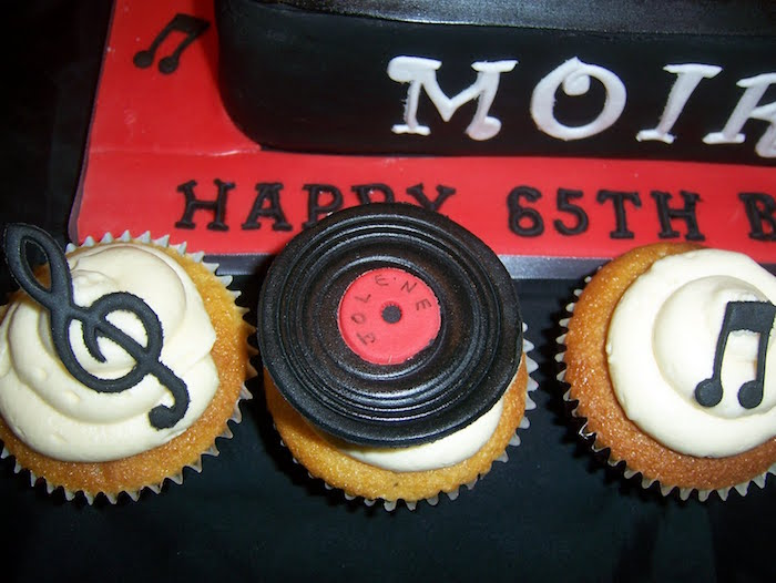 musical note in black, miniature vinyl record, and a treble clef, all made from fondant, topping three cupcakes, with white frosting