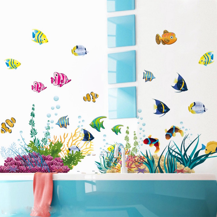 decal stickers featuring tropical fish, in many different colors, and seaweed and corals, on a white wall, near a teal and white bathtub, and four matching square glossy teal decorations, small bathroom decorating ideas