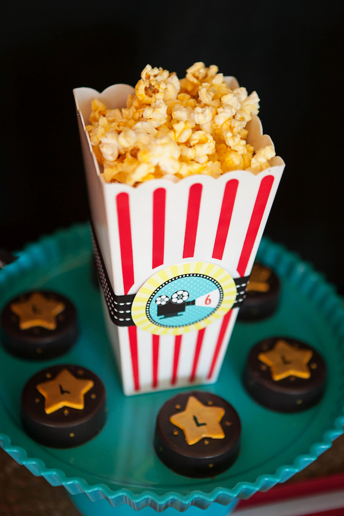 ornamental plate in pale turquoise, containing several chocolates, decorated with gold stars, and a red and white, vintage box of popcorn, 60th birthday ideas, movie theatre inspired decorations