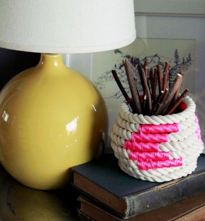 rope in off-white, decorated with hot pink thread, and wrapped around a small vase, containing shirt dried twigs, yellow lamp nearby
