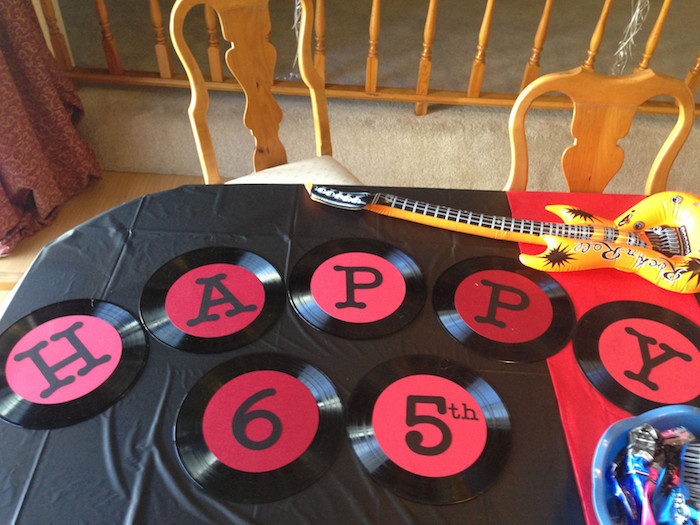 seven vinyl records, in black and red, each decorated with a letter, spelling happy 65th, placed on a table, near an inflatable guitar