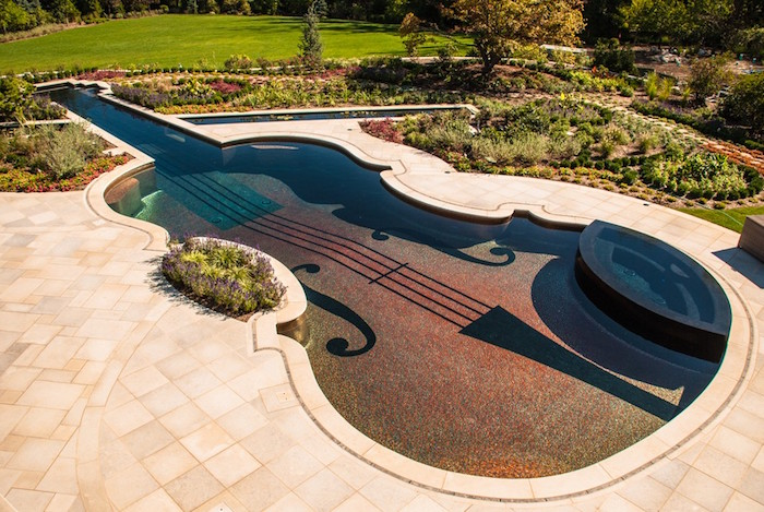 flowers planted in patterns, near a pool shaped like a violin, surrounded by pale cream tiles, backyards with pools
