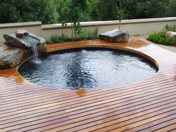 pool patio ideas, round pool surrounded by wooden planks, and decorated with large stones, water flowing into the fool, from one of the stones