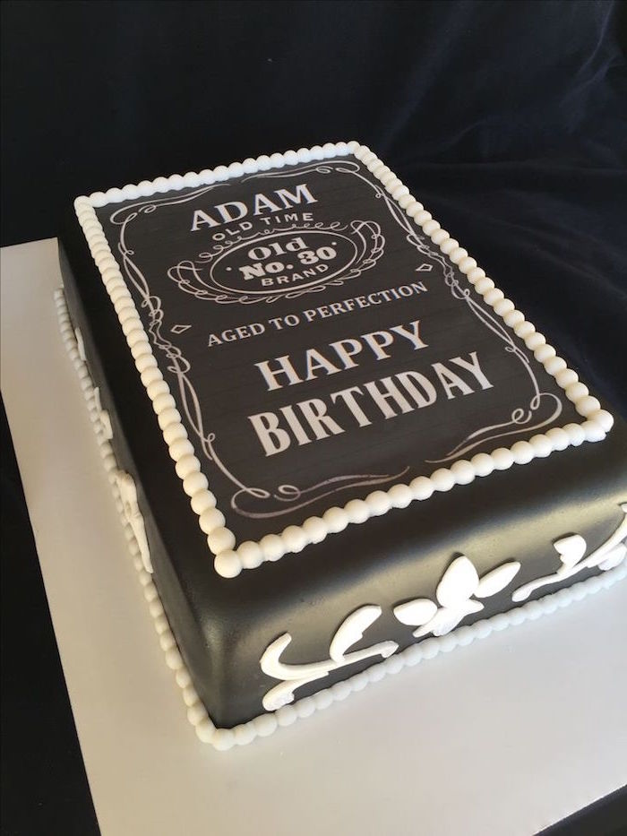 rectangular party cake, covered in smooth black fondant, and decorated with white frosting, made to look like a whiskey label, with the inscription happy 60th birthday