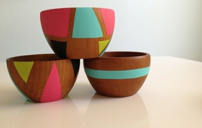 three wooden bowls, decorated with geometric shapes, in turquoise and neon pink, yellow and black, homemade gift ideas, stacked on a white surface