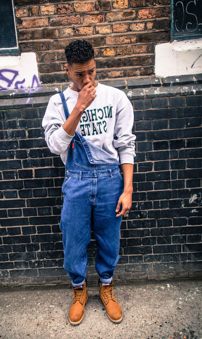 partially unbuttoned overalls, worn over a pale grey sweater, 90s outfit ideas worn by a young man, with beige worker's boots