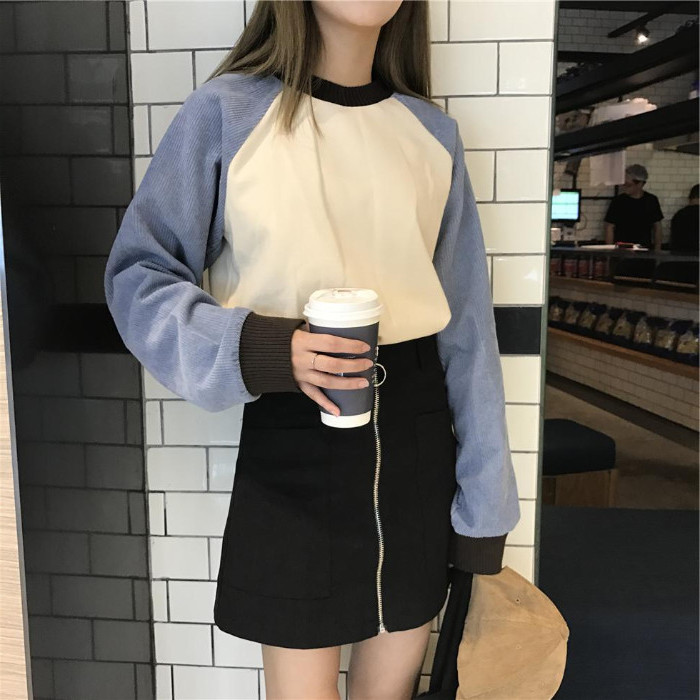 paper coffee cup, held by a brunette woman, in a black zip front miniskirt, 90s themed outfits, cream and grey retro sweater