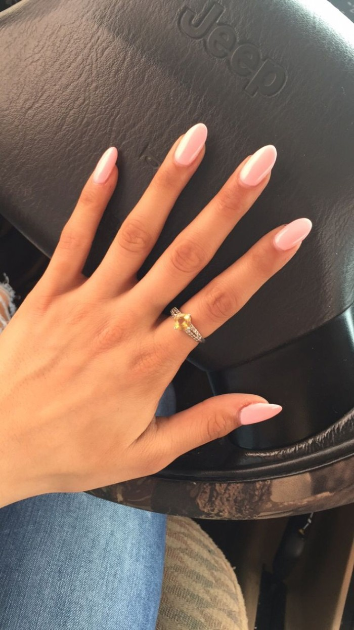 jeep steering wheel, under a slim hand, with long fingers, and oval shaped nails, painted in pale pink nail polish