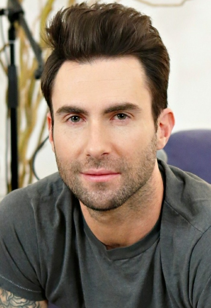 maroon 5 frontman, adam levine, with a short sides long top haircut, and stubble on his jaw, dark brunette hair styled in a quiff