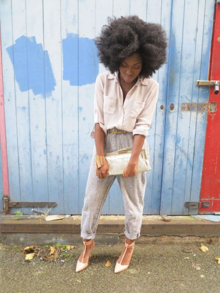 acid wash jeans with rolled bottoms, and a pale cream shirt, worn by a black woman, with a voluminous afro, in high heels and holding a large clutch bag, 80s fashion trends