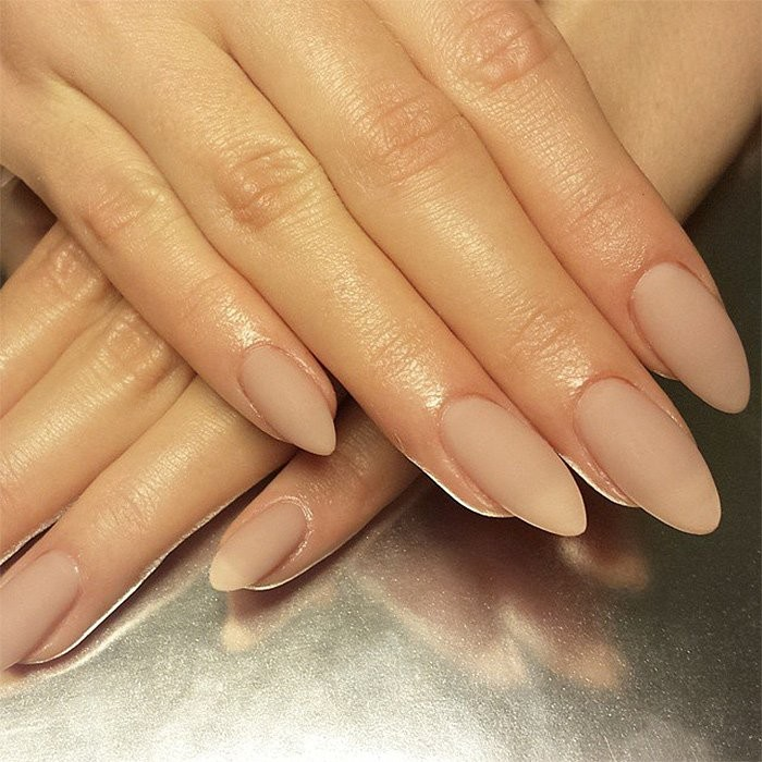 matte nail polish in nude, pinky beige, on two hands, with long fingers, and almond shaped manicure