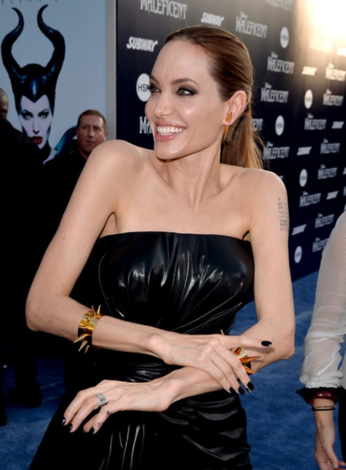 jet black short stiletto nails, worn by angelina jolie, smiling and dressed in a black, glossy sleeveless dress