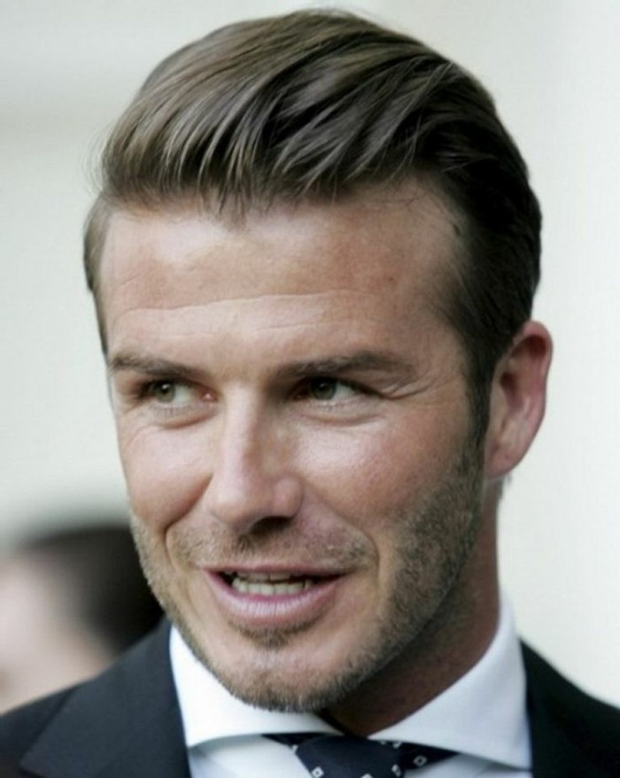 david beckham with slicked back hair, and short stubble, modern haircuts for men, smiling while looking to one side