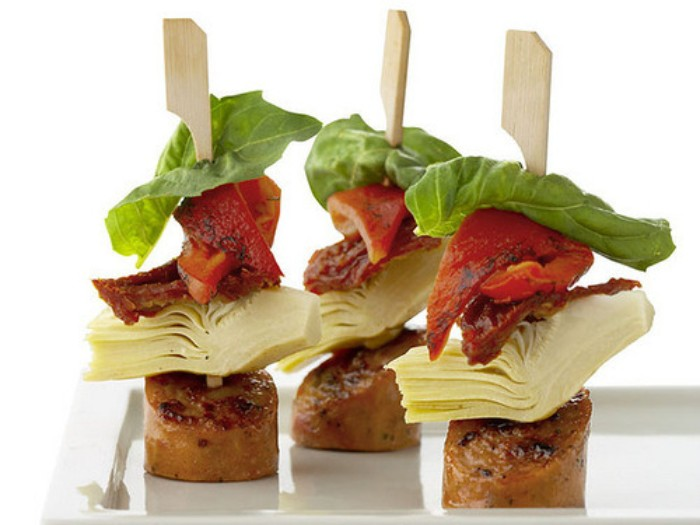 red peppers and artichoke hearts, skewered with salami and basil leaves, then grilled and served on a white plate