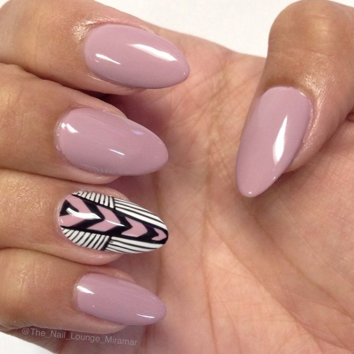hand-painted decorations in white, black and pink, on the ring finger nail of a hand, with ash pink manicure, almond nail designs