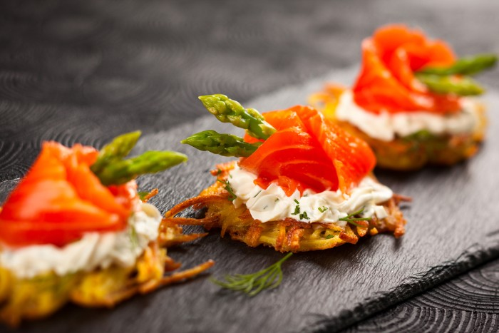 smoked salmon fillets, wrapped around asparagus tips, hor d oeuvres, on top of a cracker, with a creamy spread