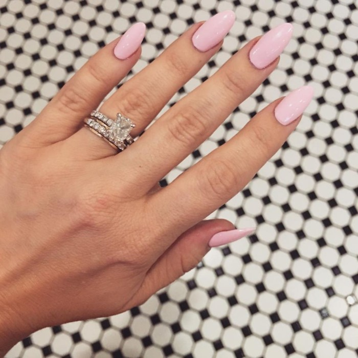 creamy pale pink nail polish, on a hand with long fingers, wearing a silver ring, with a large diamond, stiletto nails