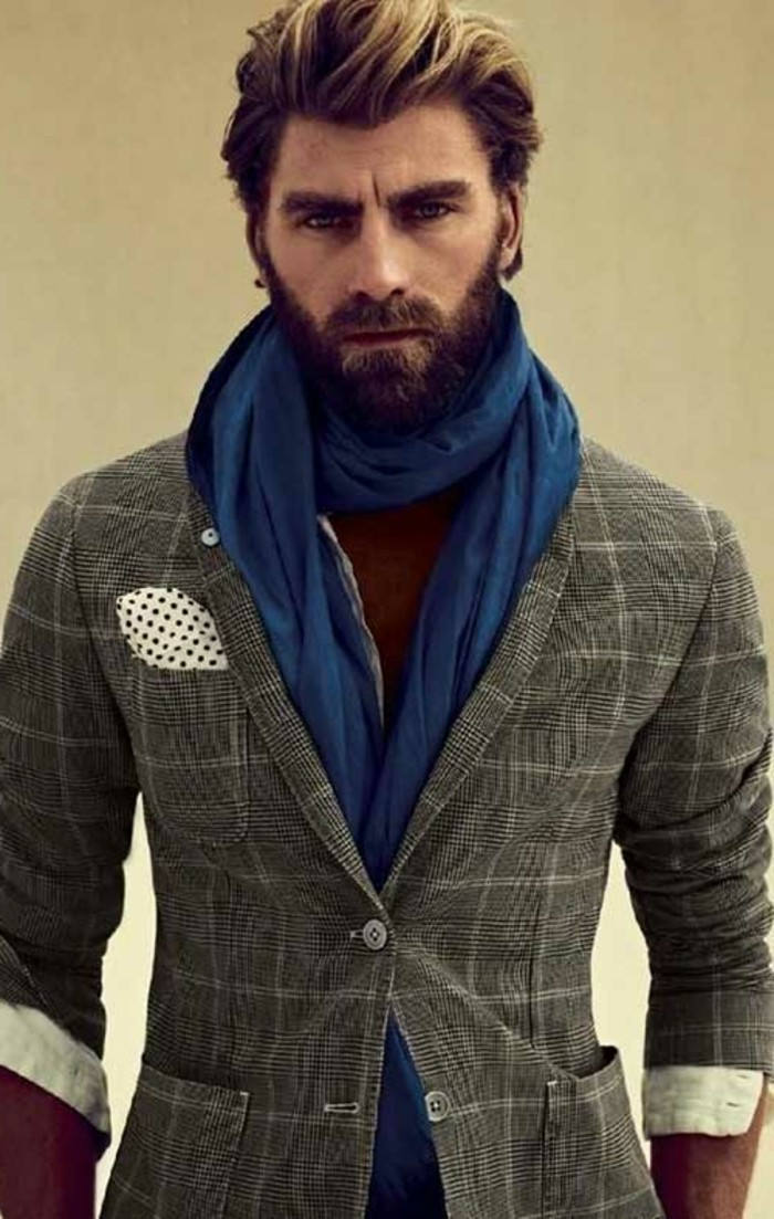 fitted grey checkered suit, worn with a white shirt, and a long blue scarf, by a bearded man, with an ombre-effect quiff, modern haircuts for men
