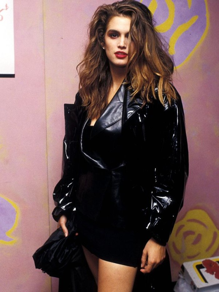 shiny black vinyl and leather jacket, worn over a black mini dress, by a young cindy crawford, 80's dress up ideas, messy wavy brunette hair, and red lipstick