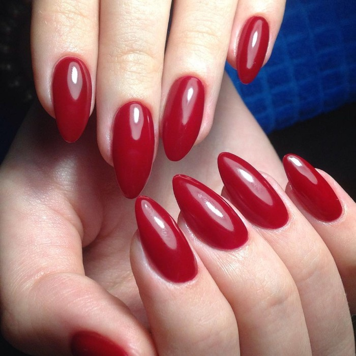deep red glossy nail polish, on almond shaped nails, worn by two pale hands, seen in close up