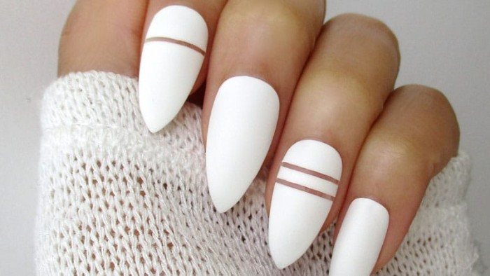 bright white nail polish, decorated with clear thin lines, on almond shaped nails, attached to a hand, gripping a white knitted sleeve