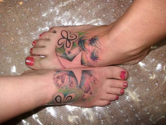 star shape formed by two foot tattoos, when they are pressed together, matching sister tattoos, with small stars and butterfly-like motifs