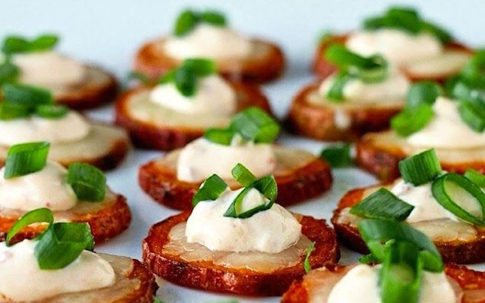 chopped green onions, on top of potato slices, roasted with their skins, and garnished with creme fraiche