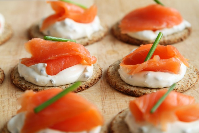 cream cheese and smoked salmon, on flat crackers, with creamy white spread, hors dourves topped with chives