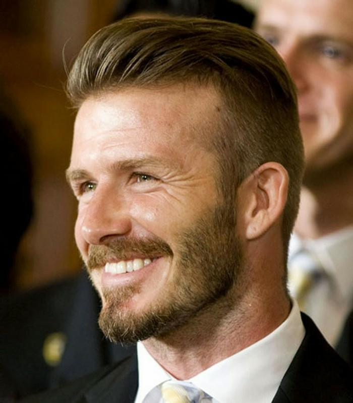 footballer david beckham, with brunette hair, styled in his trademark, slicked back quiff, short sides long top haircut, beard and mustache