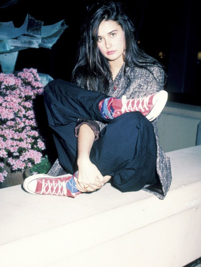 long black hair, worn by demi moore, dressed in black baggy trousers, and a patterned top, 80's fashion pictures, with colorful socks, and red converse sneakers