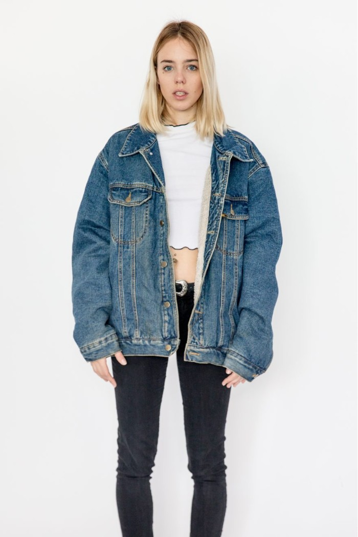 oversized denim jacket, worn over a white crop top, and dark skinny jeans, 80s fashion trends, on a young blonde woman