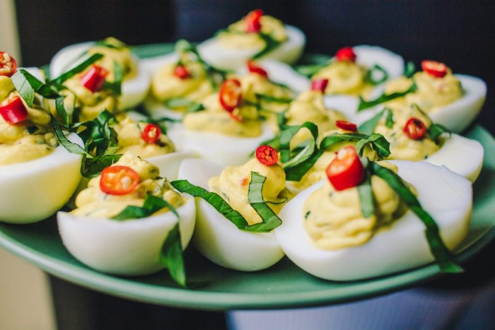 hor d oeuvres, pale blue plate, containing devlled eggs, topped with chopped fresh basil, and red chili slices