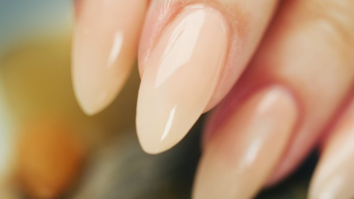 semi-tanslucent nude beige nail polish, on several glossy stiletto nails, seen in extreme close up
