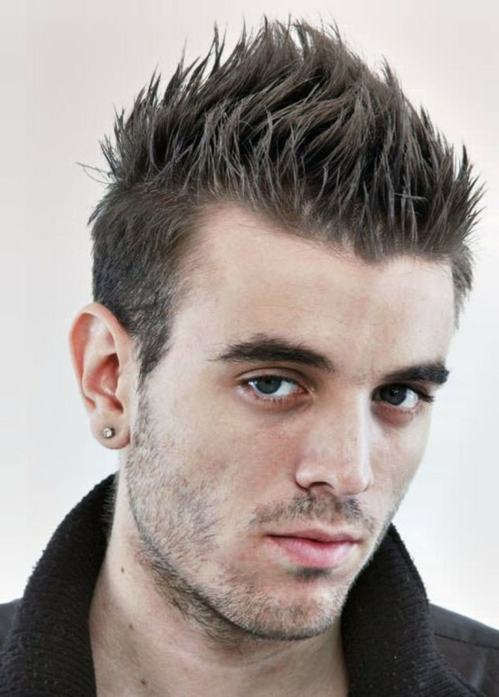 spiky faux hawk, worn by a young man, with a diamante stud earring, and stubble on his jaw and upper lip