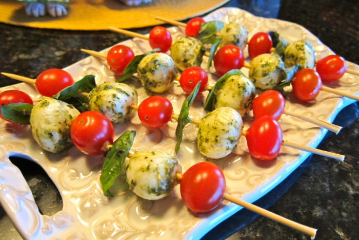 pesto-covered mozzarrella and cherry tomatoes, skewered with fresh basil leaves, hour derves, on a ceramic decoartive board