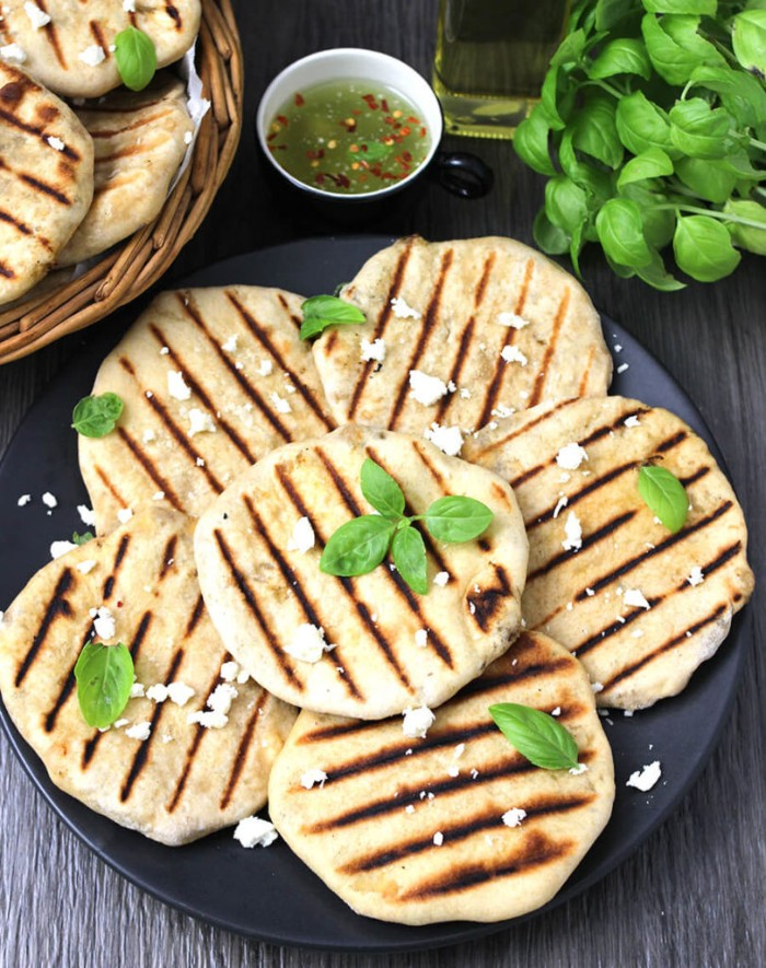 black plate containing several grilled flatbreads, topped with cheese and basil leaves, hor dourves, small dish with sauce nearby