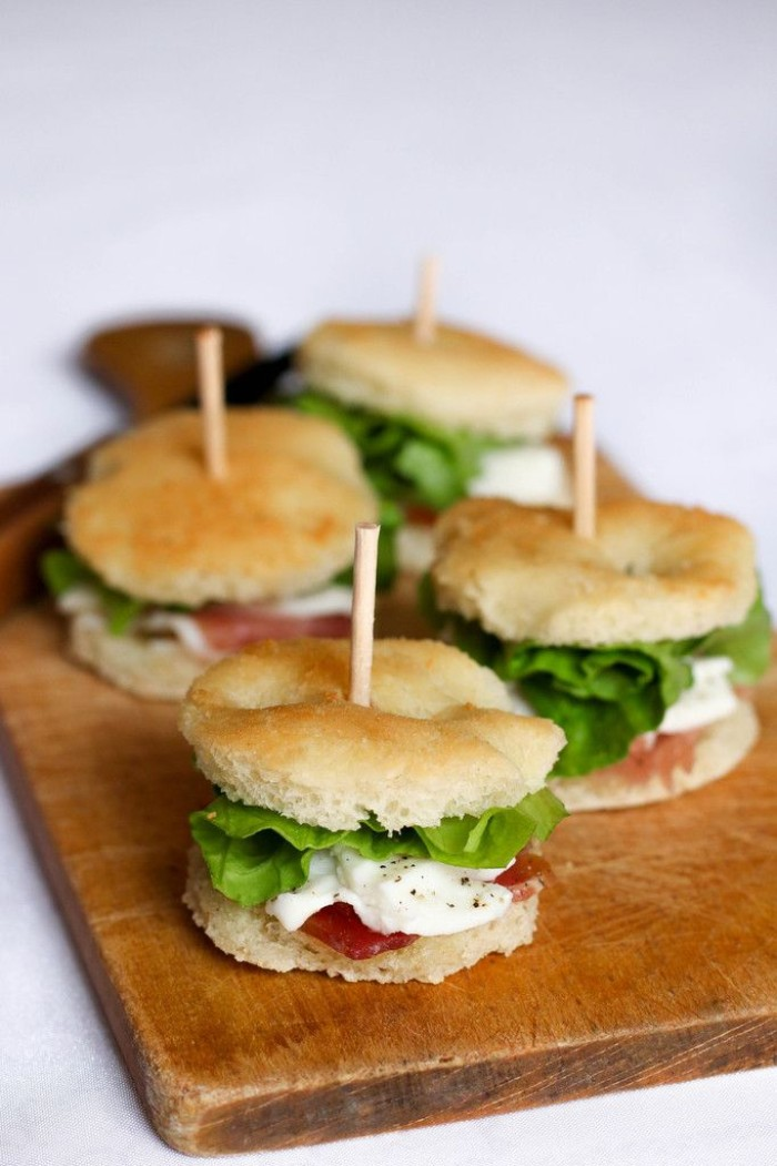 round party sized sandwiches, containing prosciutto and mozzarella, with fresh lettuce, hor dourves on a chopping board, made of wood