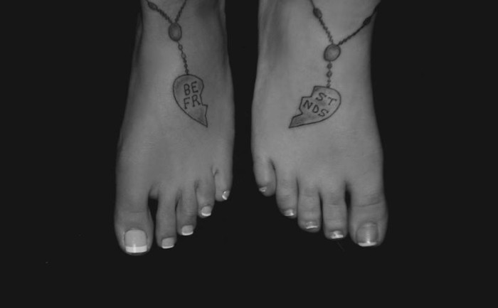 matching bestfriend tattoos, two halves of a heart-shaped friendship pendant, tattooed on two feet, standing next to each other