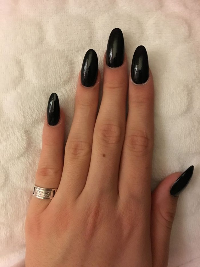 shiny black nail polish, on five long acrylic nails, attached to a hand with slender fingers, resting on a white surface