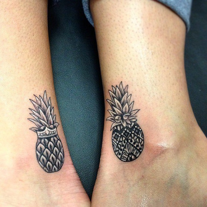matching friend tattoos, two black and grey pineapples, one wearing a crown, done near the ankle, of two feet