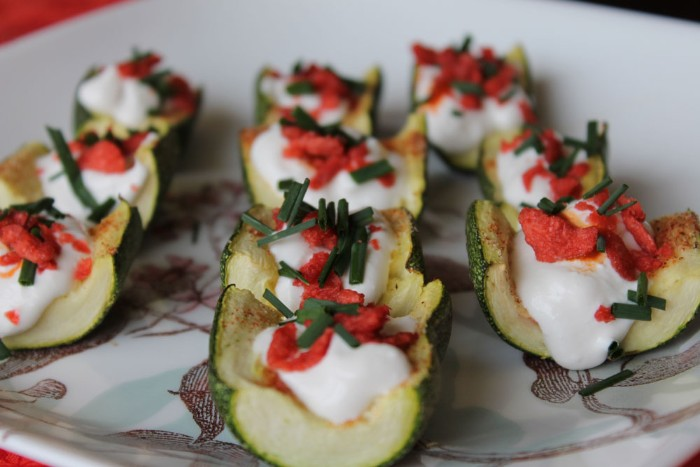 zucchini grilled and stuffed with cream cheese, garnished with chopped chives, and salsa sauce