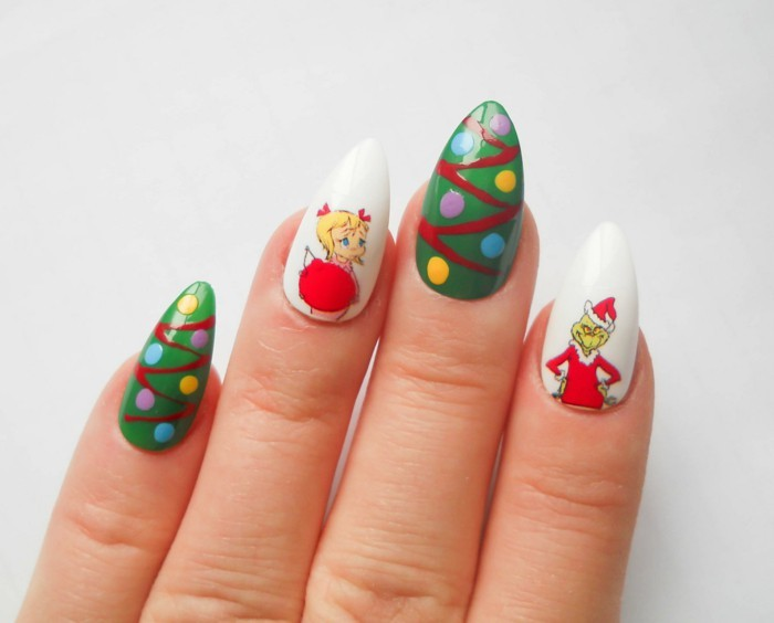 christmas-themed acrylic nail shapes, in white and green, decorated with grinch stickers, and multicolored dots