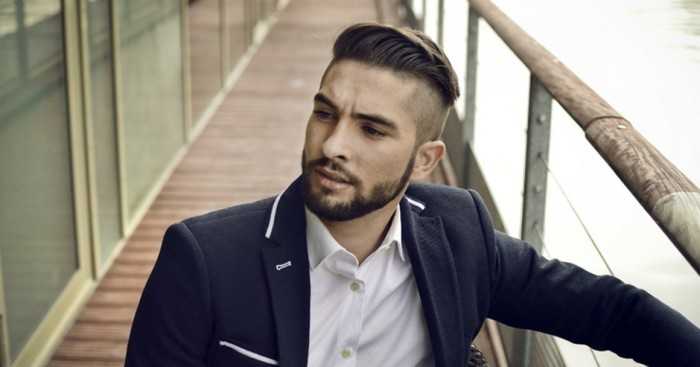 dark navy blue jacket, with white trims, worn over a white shirt, by a bearded man, with a half-pomp